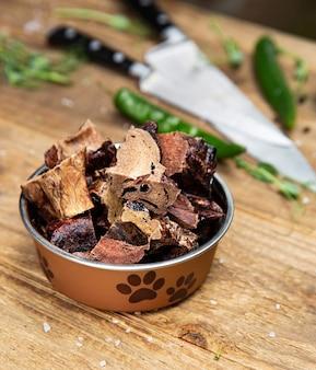 Getrocknetes leichtes rindfleisch im hundegefäß auf dem holzbrett und einigen messern auf dem hintergrund. kauen für haushunde.