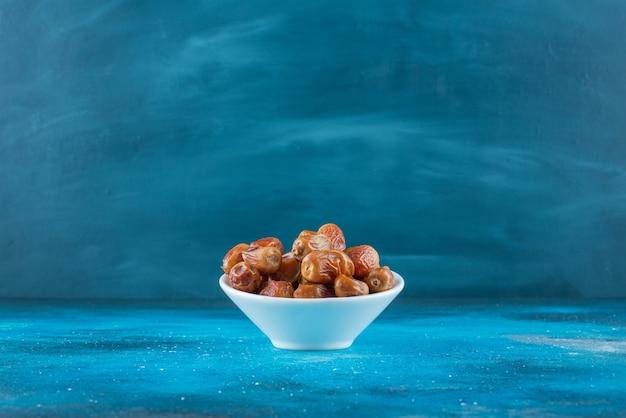 Getrocknetes oleaster in einer schüssel auf der blauen oberfläche
