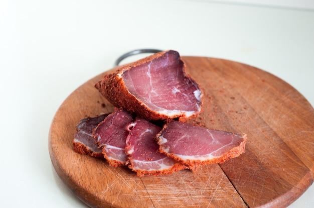 Getrocknetes rindfleisch. geschnittenes rindfleisch ruckartig. fleisch auf einem holzbrett.