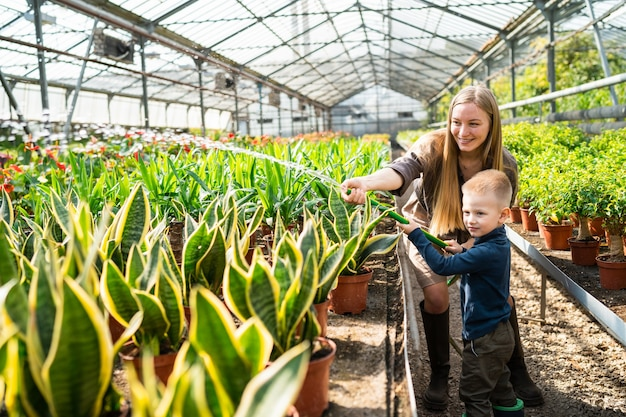 Gewächshausarbeiterin und ihr sohn gießen die pflanzen mit einem schlauch