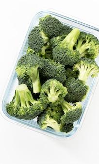 Gewaschene und geschnittene brokkolikrone im glasbehälter. bio-brokkoli, zerkleinert und bereit zum kochen.