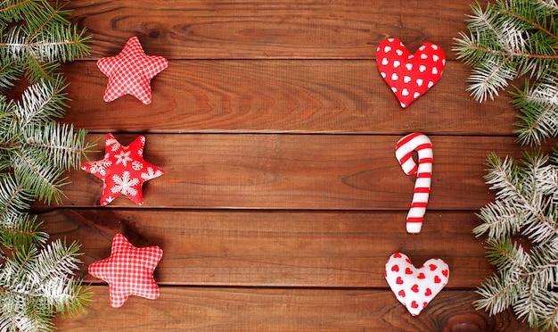 Gewebe-weihnachtsspielwaren auf einem holz- und weihnachtsbaumhintergrund