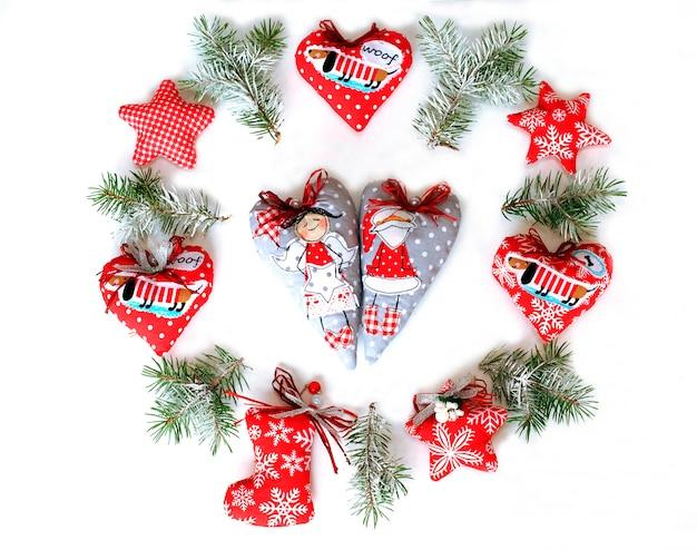 Gewebe-weihnachtsspielwaren auf einem weißen hintergrund und einem weihnachtsbaum