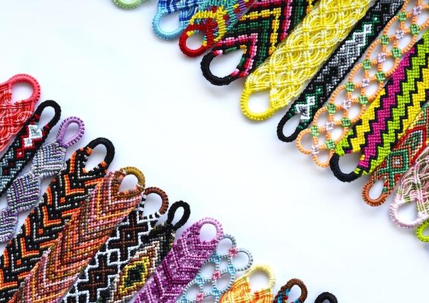 Gewebte diy-freundschaftsarmbänder, handgefertigt aus hellem stickgarn mit knoten auf weißem hintergrund