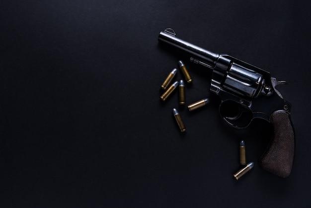 Gewehr mit kugeln auf schwarzem hintergrund