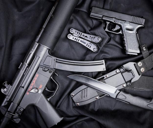 Gewehr, pistole, messer mit scheide, kompass und notizbuch mit stift an auf schwarzem stoff