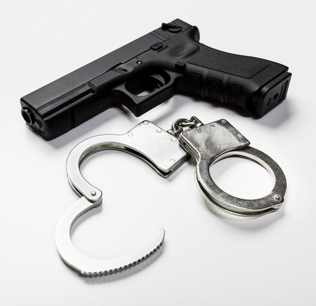 Gewehr und handschellen auf weißem hintergrund