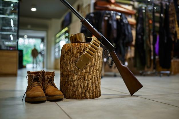 Gewehr und jagdstiefel am stumpf im waffenladen, niemand. waffenshop-interieur im hintergrund, munitionssortiment, schusswaffenauswahl, schießhobby und lifestyle, selbstschutz und sicherheit