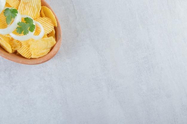 Gewellte chips verziert mit zwiebelringen in keramikplatte.