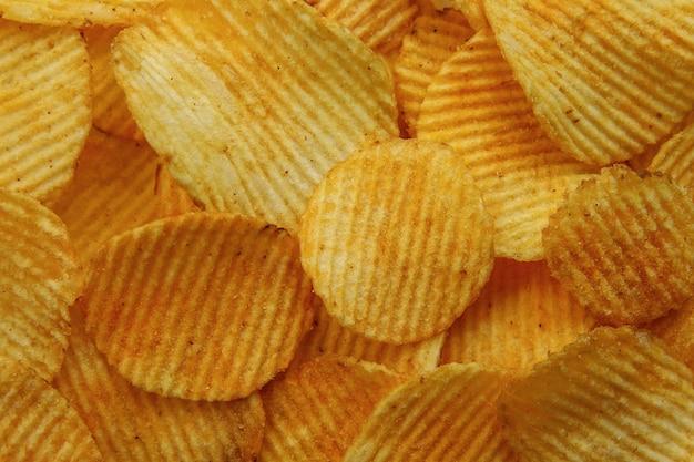 Gewellte kartoffelchips. lebensmittel textur hintergrund. ansicht von oben.