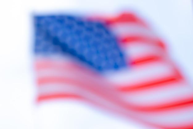 Gewellter und unscharfer fokus der flagge der vereinigten staaten von amerika mit weißem hintergrund