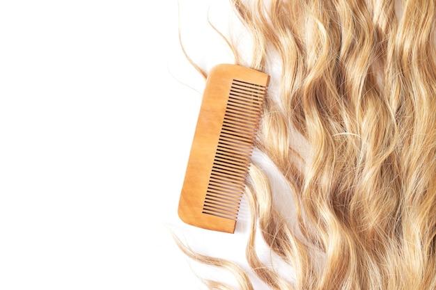 Gewelltes blondes haar mit bambuskamm isoliert auf weißem hintergrund draufsicht