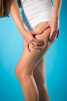 Gewicht verlieren, junge frau, die ihr bein überprüft
