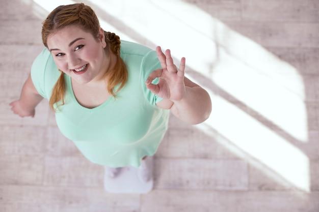 Gewichtskontrolle. pralle junge frau, die ihr gewicht prüft, während sie das ergebnis zeigt