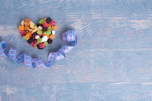 Gewichtskontrollkonzept. diät-lebensmittel-konzept. getrocknete früchte und nüsse in form eines herzens und eines maßbandes sehen aus wie ein lächeln auf einem blauen hölzernen hintergrund, draufsicht, kopierraum