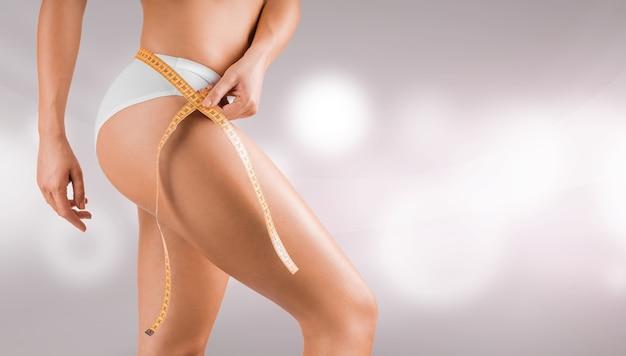Gewichtsverlust-diätkonzept mit jungen frauen, die mit maßband um ihre taille posieren