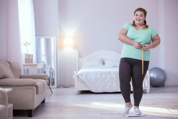 Gewichtsverlust. erfreute junge frau, die auf waage steht, während sie ihre ergebnisse zeigt
