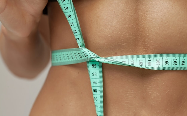Gewichtsverlust, schlanker körper, gesundes lebensstilkonzept. fit fitness-mädchen messen ihre taille mit maßband auf grau