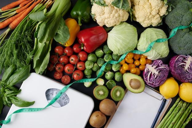 Gewichtsverlustskala mit gemüse und obst. diätkonzept. draufsicht.