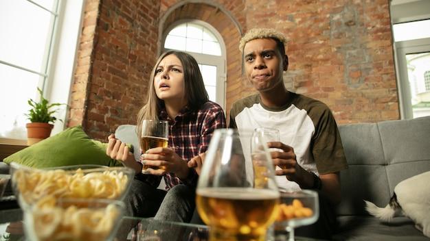 Gewinnen. aufgeregtes paar, freunde, die sportmatches sehen, meisterschaft zu hause. multiethnische freunde, fans, die ihre lieblingssportmannschaft anfeuern