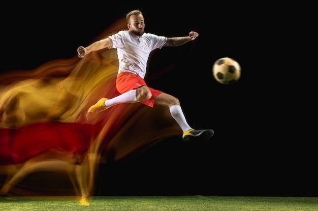 Gewinnen. junger kaukasischer männlicher fußball- oder fußballspieler in sportbekleidung