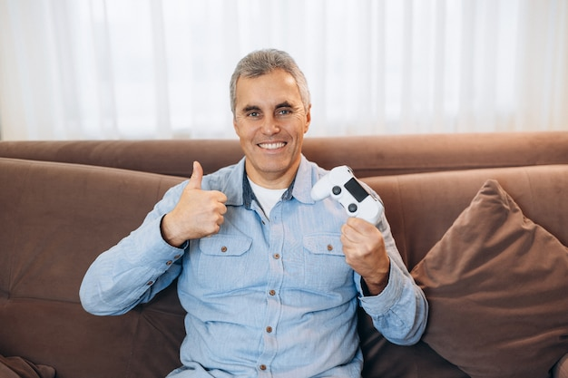 Gewinnen sie im videospiel mann mittleren alters, der seinen gamecontroller zeigt, daumen hoch, mit zähnen lächelt und in die kamera schaut. der fröhliche mann freut sich über eine angenehme party in seinem lieblingsspiel.