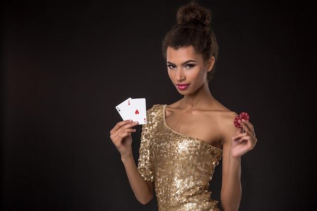 Gewinnende frau - junge frau in einem noblen goldenen kleid, das zwei asse und zwei rote chips hält, eine kartenkombination des pokers der asse.