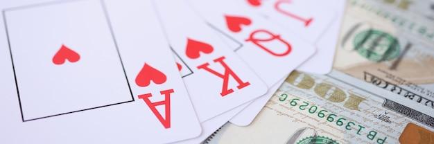 Gewinnende kombination von spielkarten, die auf viel amerikanischer dollarnahaufnahme liegen. pokerspielkonzept