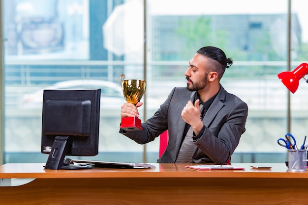 Gewinnende pokaltrophäe des geschäftsmannes im büro