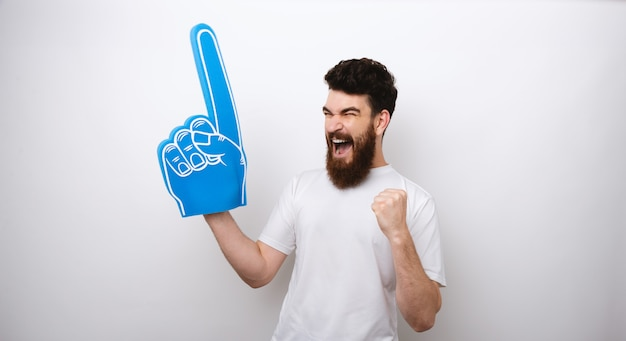 Gewinner bärtiger mann mit einem blauen schaumfinger, der voller glück schreit.