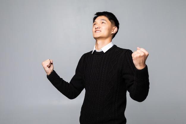 Gewinner des jungen chinesischen mannes lokalisiert auf weißer wand