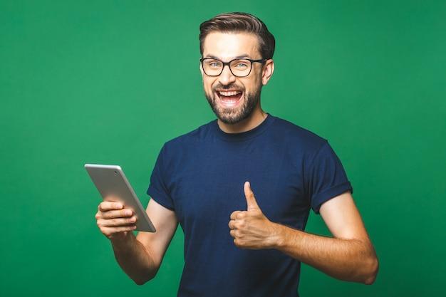 Gewinner! glücklicher junger mann im freizeithemd und in den gläsern, die tablette über grünem hintergrund stehen und verwenden. daumen hoch.