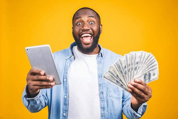 Gewinner! junger reicher afroamerikanermann im lässigen t-shirt, das gelddollarscheine mit überraschung hält