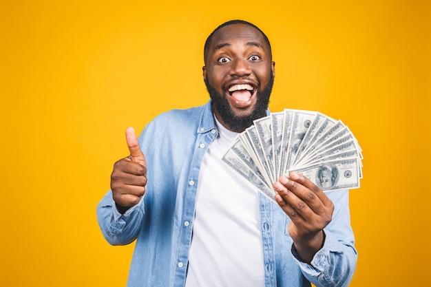 Gewinner! junger reicher afroamerikanermann im lässigen t-shirt, das gelddollarscheine mit überraschungs-daumen hoch hält.