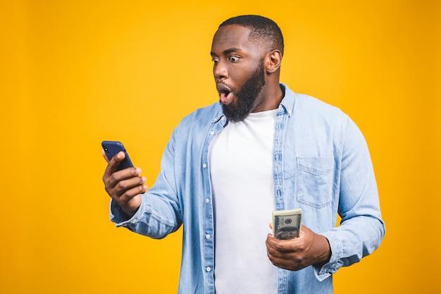 Gewinner! junger reicher afroamerikanermann im lässigen t-shirt, das gelddollarscheine und handy mit überraschung hält