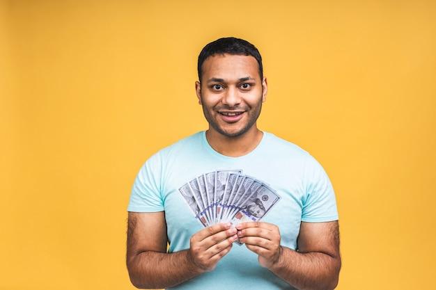 Gewinner! junger reicher glücklicher afroamerikanischer indianischer schwarzer mann in lässigem halten von gelddollarscheinen mit überraschung isoliert über gelbem wandhintergrund.