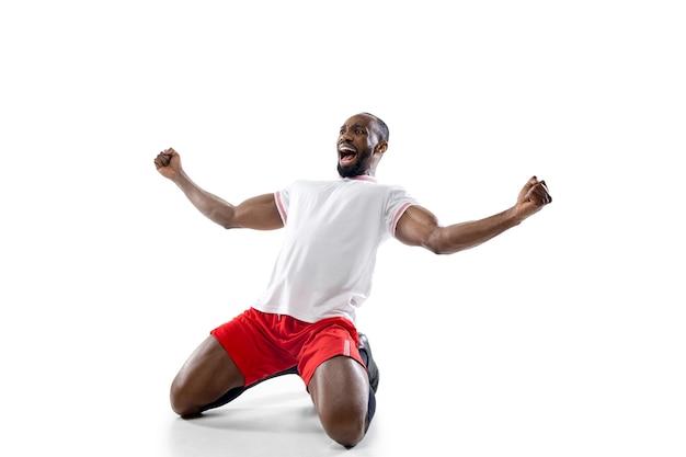 Gewinner. lustige gefühle des professionellen fußballspielers lokalisiert auf weißem studiohintergrund. spannung im spiel, menschliche emotionen, gesichtsausdruck und leidenschaft mit sportkonzept.
