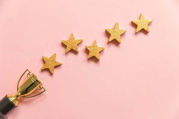 Gewinner oder champion gold trophy cup und sterne bewertung isoliert auf rosa pastell