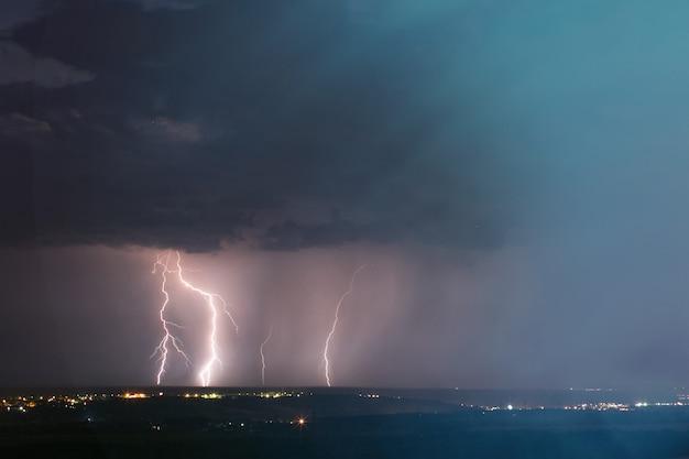 Gewitter über der stadt. blitzschlag über dunkelblauem himmel in der nachtstadt.