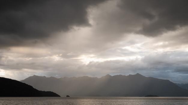 Gewitterwolken sammeln sich über dem see und der bergkette kepler track neuseeland