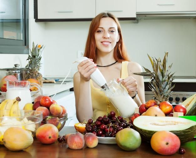 Gewöhnliche frau kocht milchshake mit früchten
