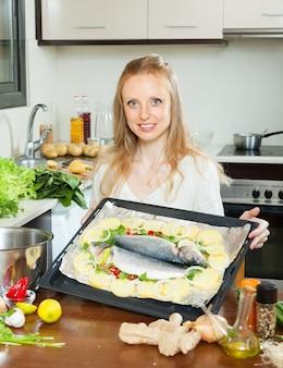 Gewöhnliche hausfrau, die fische und kartoffeln kocht