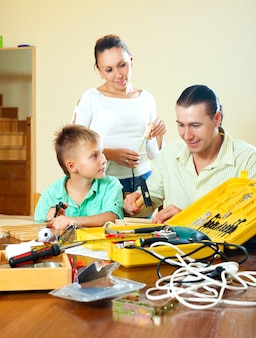 Gewöhnliche nette dreiköpfige familie, die etwas mit den arbeitsgeräten macht