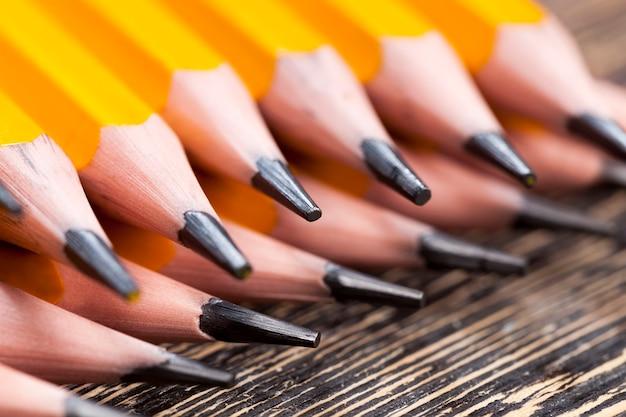 Gewöhnlicher gelber holzstift mit grauer weicher mine zum zeichnen und für kreativität, nahaufnahme von stiften nach dem schärfen, bleistift aus natürlichen materialien