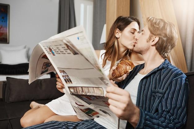 Gewöhnlicher tag von zwei verliebten erwachsenen menschen, die zusammen gehen und ihre freizeit zu hause verbringen. mann will zeitung lesen, aber freundin lenkt ihn mit einem kuss ab und bietet bisscroissant an, das sie in der hand hält