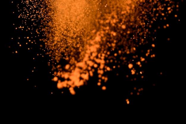 Geworfenes buntes pulver auf schwarzem hintergrund