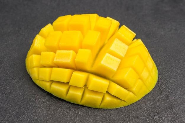 Gewürfelte mangostücke. tropische früchte. gesunde ernährung. flach liegen nahaufnahme. schwarze oberfläche