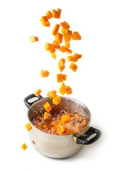 Gewürfelter kürbis, der in einen kochenden topf fällt