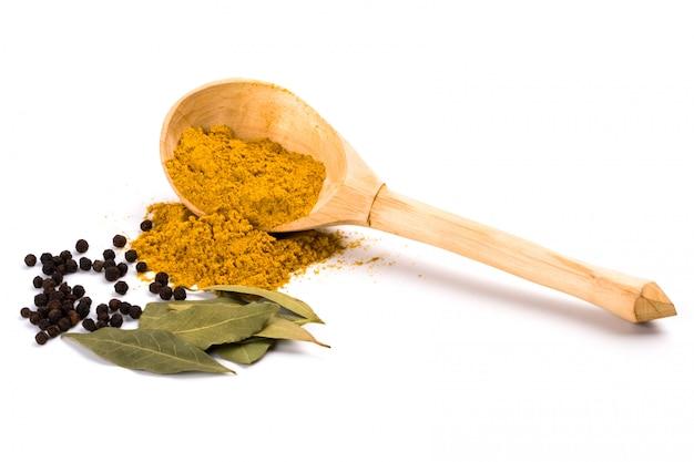 Gewürze: curry auf hölzernem löffel, pfeffer, lorbeerblätter lokalisiert auf weißem hintergrund