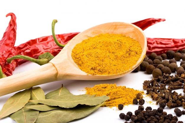 Gewürze: curry auf holzlöffel, pfeffer, piment, nelken und lorbeerblättern auf weißem hintergrund